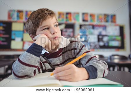 Thoughtful boy studing while sitting at desk at classroom