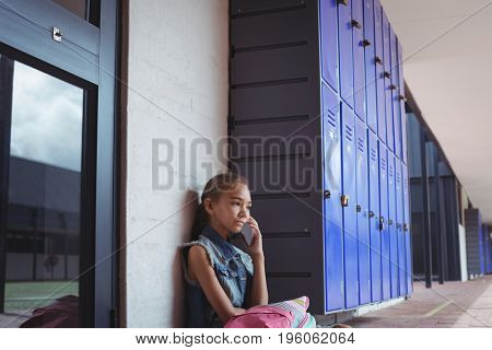 Elementary schoolgirl talking on mobile phone while sitting by lockers at school