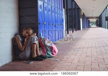 Full length of elementary schoolgirl resting by lockers in corridor at school