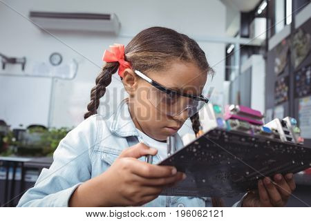 Concentrated elementary student examining circuit board on desk at electronics lab