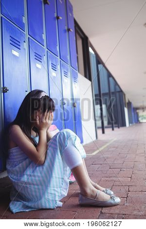 Side view of schoolgirl covering face with hands while sitting by lockers at school