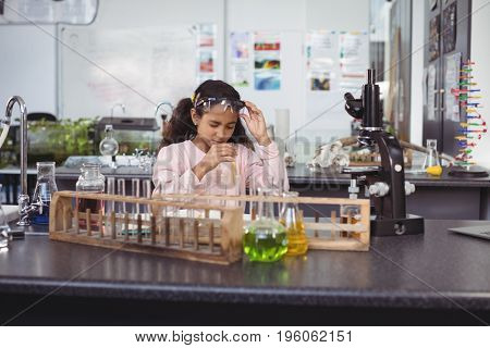 Elementary student holding test tube by desk at science laboratory