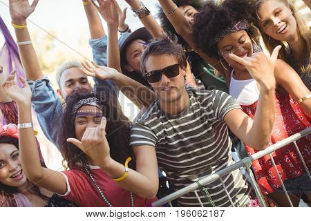 Happy young man gesturing shaka signs while enjoying with friends at music festival