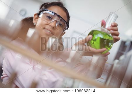 Portrait of elementary student holding green chemical in glass beaker at science laboratory