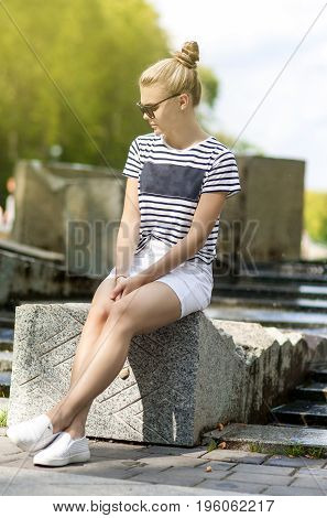 Teenager Concepts. Portrait of Shy and Sensual Caucasian Teenage Girl Posing in Green Summer Park and Wearing Sunglasses. Sitting on Long Stone. Vertical Image Composition
