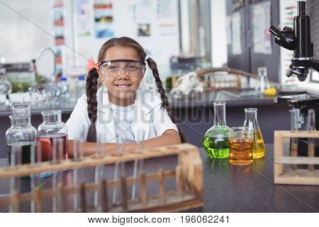 Portrait of elementary student wearing protective eyewear by desk at science laboratory