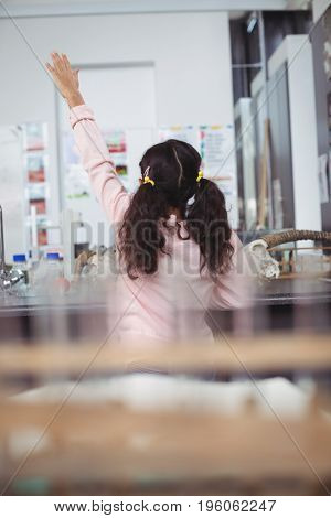 Rear view of elementary schoolgirl raising hand by desk at science laboratory