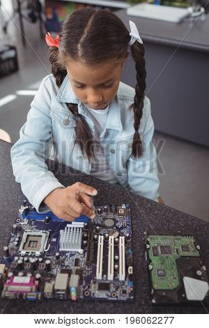 High angle view of elementary girl assembling circuit board on desk at electronics lab