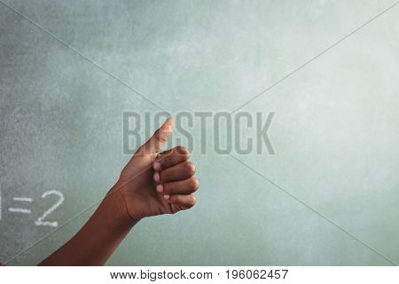 Cropped hand of student showing thumb against blackboard in classroom