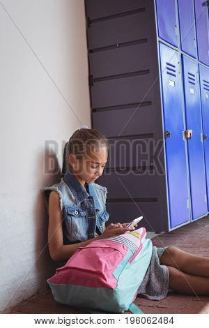 Elementary schoolgirl using mobile phone while sitting by lockers at school