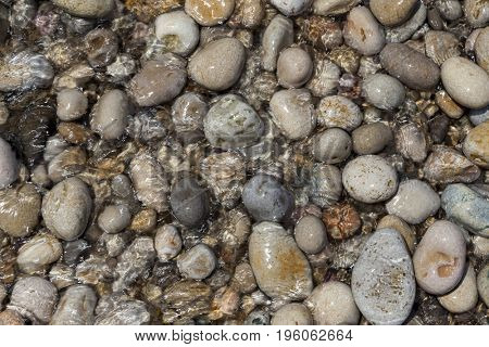Large wet sea pebbles. Stone background for tiles, facades of houses