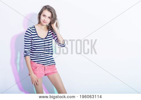 Youth Lifestyle Concepts and Ideas. Portrait of Caucasian Brunette Girl in Striped Shirt with Lifted hand. Touching Head. Horizontal Shot