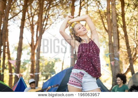 Young woman standing with arms raised against trees at campsite