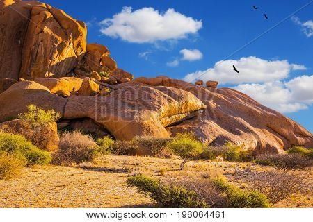 The massive granite outcrops in the Namib Desert. Stone of Spitzkoppe, Namibia. Play of light and shadow on the rocks. Concept of extreme and ecological tourism