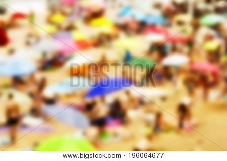 a defocused blur background of a packed beach in summer