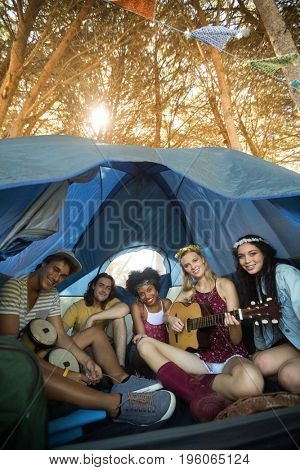 Portrait of happy friends enjoying while sitting together in tent on sunny day