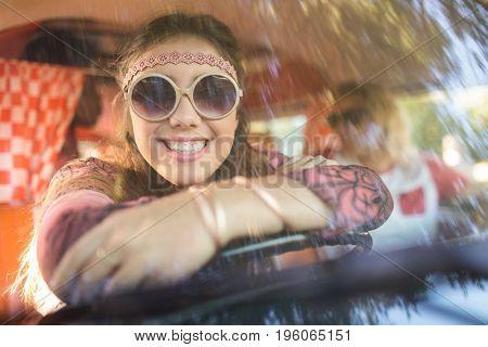 Portrait of smiling woman sitting in camper van seen through windshield
