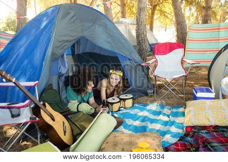 Couple talking while relaxing in tent at campsite