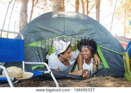 Happy couple talking while relaxing in tent at campsite