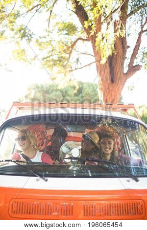 Happy friends sitting in camper van seen through windshield