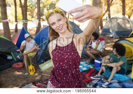 Happy woman taking selfie while standing on field at campsite