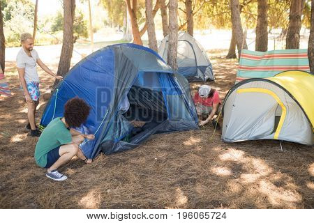 Friends setting up tent on field