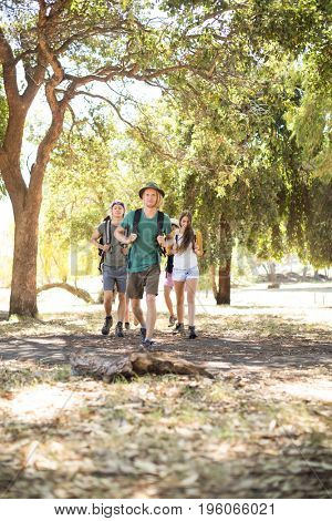 Friends with backpack walking on field amidst tree
