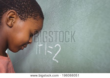 Student leaning on chalkboard in classroom
