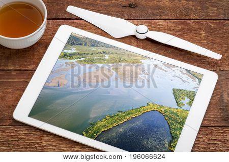 aerial view of lower Niobrara River in Nebraska Sandhills, reviewing image on a digital tablet