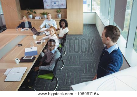 Serious business entrepreneur explaining strategy to colleagues in meeting room at office poster