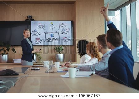 Businesswoman interacting with team during meeting at conference table in board room