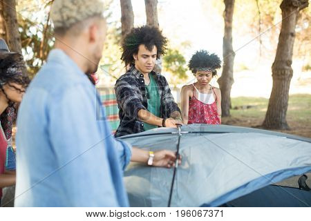 Young friends setting up tent at campsite