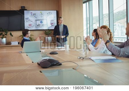 Colleagues clapping during meeting in board room