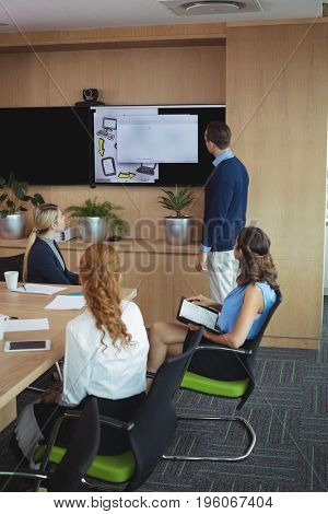 Business people looking at device screen during meeting in board room