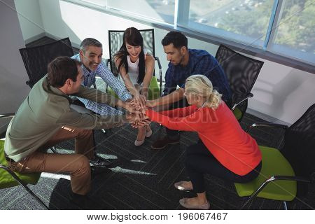 High angle view of business colleagues stacking hands while sitting on chairs by window at office
