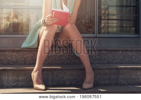 Close up of woman with beauty leg holding a book on the street