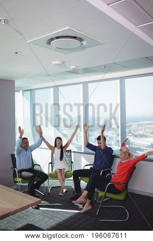 Cheerful business people with arms raised sitting on chairs by window at office