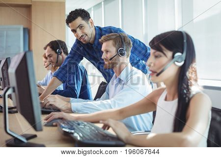 Smiling male supervisor assisting telemarketer at desk in call center