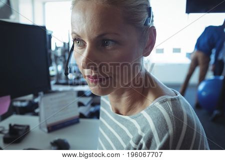 Thoughtful businesswoman looking away at office desk