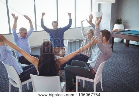 Cheerful business colleagues with arms raised sitting on chairs at office