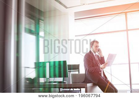 Mature businessman holding document while talking on mobile phone in office