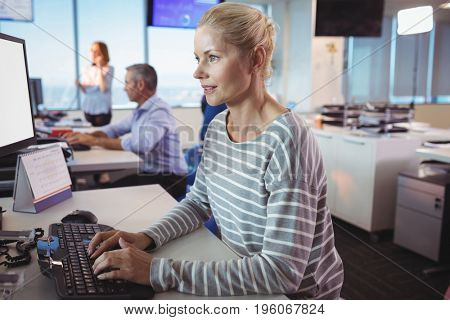Concentrated businesswoman typing on keyboard at desk in office