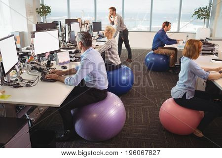 Business people sitting on exercise balls while working at desk in office