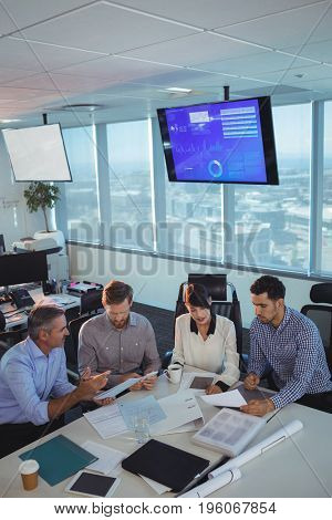 High angle view of business partners discussing in meeting at office desk