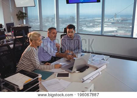 Business partners discussing over laptop at office desk in meeting