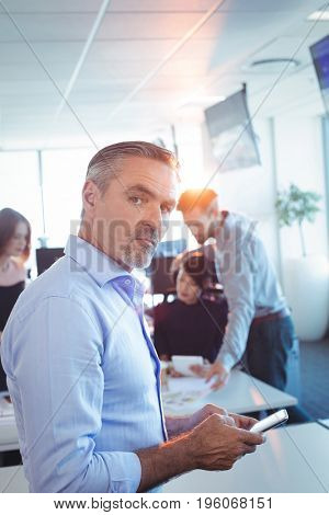 Portrait of businessman using mobile phone at office