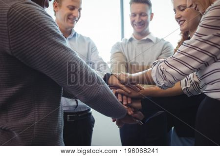 Happy business colleagues stacking hands at office