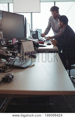 Young male business colleagues discussing over documets at desk in office