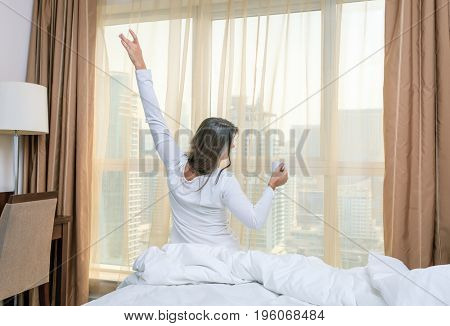 Mature woman is waking up in her bedroom in a hotel/apartment