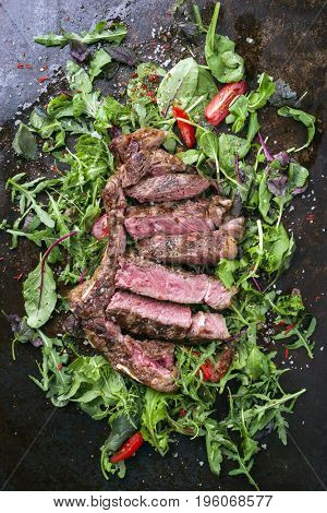 Traditional Italian tagliata di manzo with lettuce and tomatoes as close-up on an old rusty metal sheet